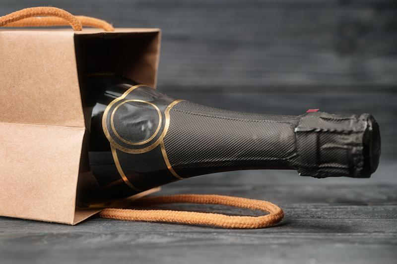 Sparkling wine in craft gift bag on black wooden background. Toned image with selective focus