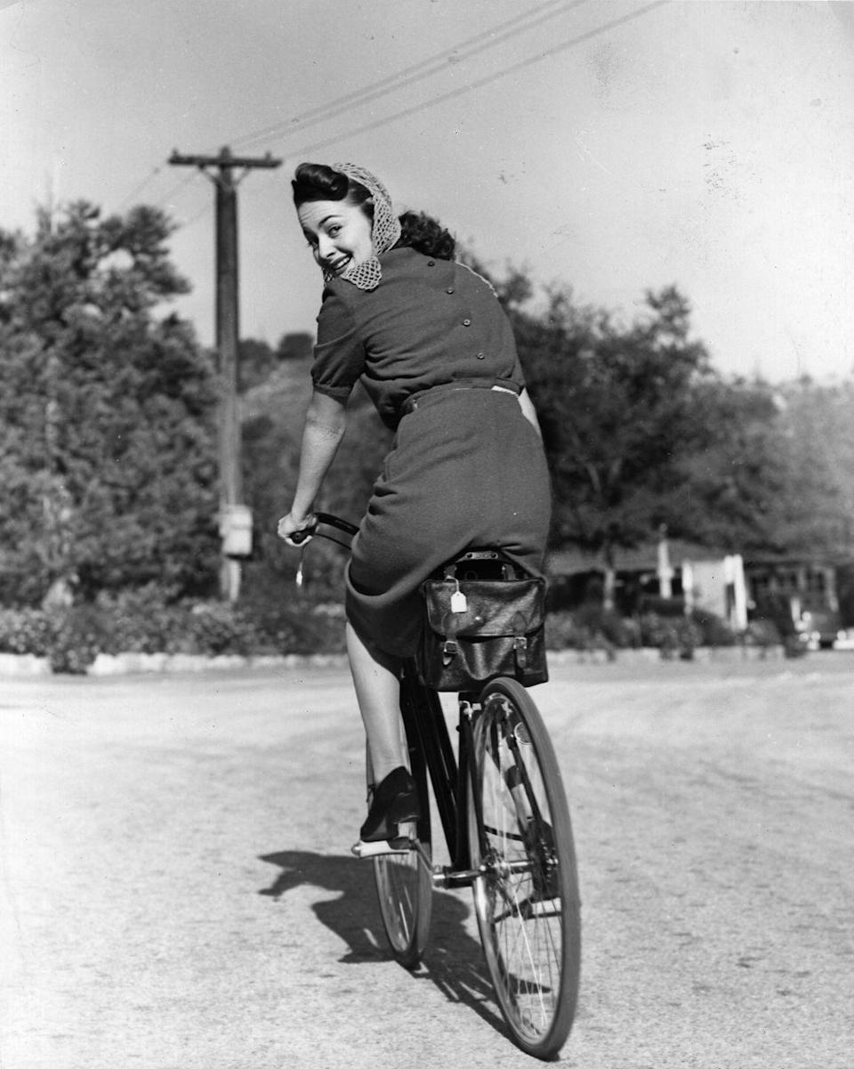 <p>The actress, circa 1938, glances back at the photographer while riding her bike. </p>