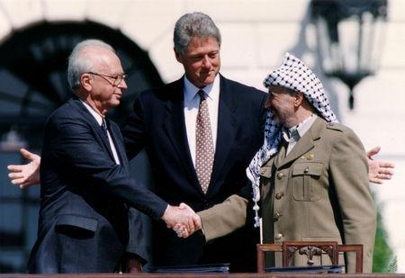 FILE PHOTO: PLO Chairman Yasser Arafat (R) shake hands with Israeli Prime Minister Yitzhak Rabin (L), as U.S. President Bill Clinton stands between them, after the signing of the Israeli-PLO peace accord, at the White House in Washington, U.S., September 13, 1993. REUTERS/Gary Hershorn/File Photo