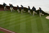 Grounds crew members place a tarp over the infield at Oriole Park at Camden Yards prior to a baseball game between the Baltimore Orioles and the Seattle Mariners, Monday, April 12, 2021, in Baltimore. (AP Photo/Julio Cortez)