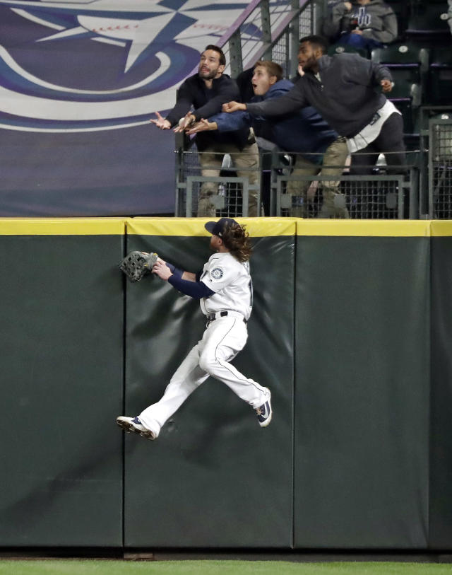 Seattle Mariners right fielder Ben Gamel leaps at the wall as the ball slips from the grasp of fans after a grand slam by Oakland Athletics' Matt Olson during the fifth inning of a baseball game Wednesday, Sept. 26, 2018, in Seattle. (AP Photo/Elaine Thompson)