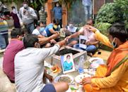 Fans of Amitabh Bachchan perform a prayer service (hawan) for his speedy recovery from COVID-19, outside a temple on Bhootnath Road, on July 12, in Patna, India. (Photo by Santosh Kumar/Hindustan Times via Getty Images)