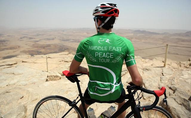 A cyclist stands on the cliff of the Machtesh Ramon crater in the southern Israeli Negev desert after riding on the fourth day of the Middle East Peace Tour pre-Event on April 27, 2017 (AFP Photo/MENAHEM KAHANA)