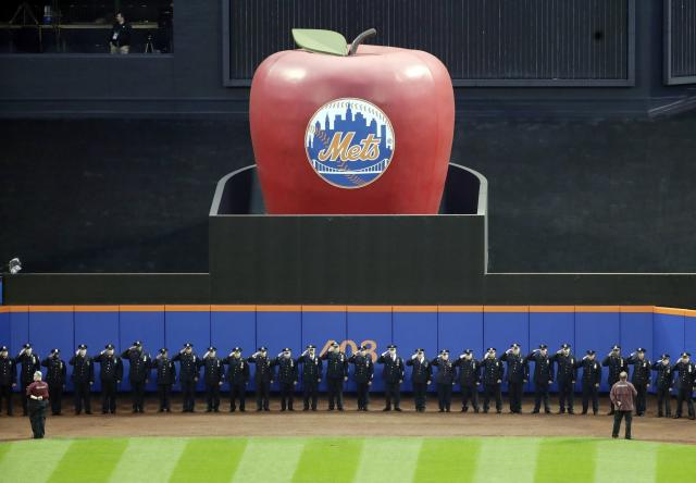 Members of the New York Police Department salute during the pregame ceremony of a baseball game between the New York Mets and the Miami Marlins, Tuesday, Sept. 11, 2018, in New York. (AP Photo/Frank Franklin II)
