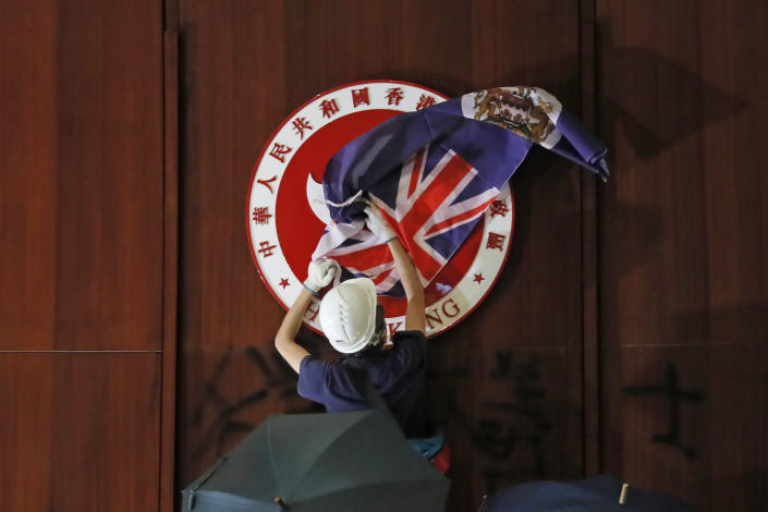 FILE - In this Monday, July 1, 2019, file photo, a protester covers the Hong Kong emblem with a Hong Kong colonial flag after they broke into the Legislative Council building in Hong Kong. Protesters smashed glass windows, sprayed rude graffiti and defaced Hong Kong's official emblem with black paint. But of all the dramatic photos showing hundreds of young protesters storming the city's parliament this week, one image makes for particularly uncomfortable viewing in Beijing: The British colonial flag draped aloft a podium in parliament's chamber. (AP Photo/Kin Cheung, file)