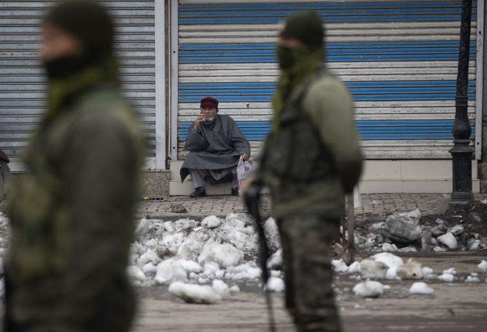 Indian paramilitary soldiers stand guard as a Kashmiri man smokes outside a closed shop in Srinagar, Indian controlled Kashmir, Tuesday, Feb. 9, 2021. Businesses and shops have closed in many parts of Indian-controlled Kashmir to mark the eighth anniversary of the secret execution of a Kashmiri man in New Delhi. Hundreds of armed police and paramilitary soldiers in riot gear patrolled as most residents stayed indoors in the disputed region's main city of Srinagar. (AP Photo/Mukhtar Khan)