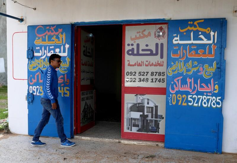 A man walks past a real estate office in Tripoli
