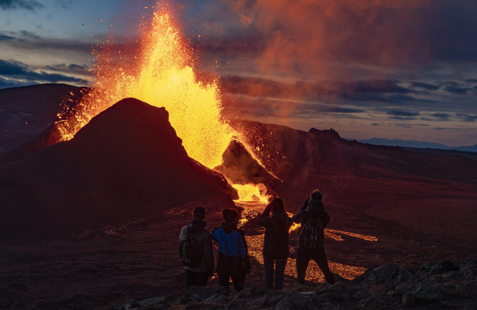 People watch as lava flows from an eruption of the Fagradalsfjall volcano on the Reykjanes Peninsula in southwestern Iceland on Wednesday, May 12, 2021. The glow from the bubbling hot lava spewing out of the Fagradalsfjall volcano can be seen from the outskirts of Iceland's capital, Reykjavík, which is about 32 kilometers (20 miles) away. Pandemic or no pandemic, the world will never stand still. That's perhaps no clearer than in Iceland where the Fagradalsfjall volcano has awoken from a slumber that has lasted 6,000 years, give or take a year or two. (AP Photo/Miguel Morenatti)
