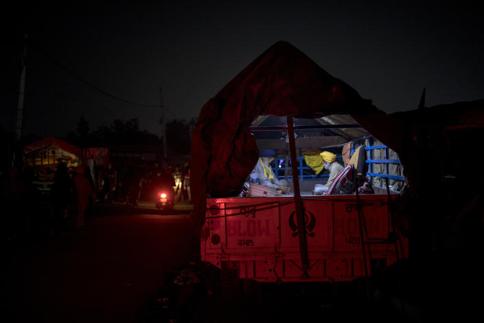 """Karmat Singh, 62, right, and Joginder Singh, 77, pray inside their tractor trailer parked on a highway as they join a protest against new farm bills, at the Delhi-Haryana state border, India, Wednesday, Dec. 2, 2020. The convoy of trucks, trailers and tractors stretches for at least three kilometers (1.8 miles) with farmers who have hunkered down, supplied with enough food and fuel to last weeks. Their rallying call is """"Inquilab Zindabad"""" (""""Long live the revolution""""). (AP Photo/Altaf Qadri)"""