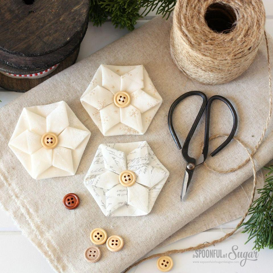 """<p>With just a little bit of sewing know-how (no machine needed!), you can craft these professional-looking fabric stars. </p><p><em>Get the tutorial at <a href=""""http://aspoonfulofsugardesigns.com/2016/12/folded-hexagon-ornament/"""" rel=""""nofollow noopener"""" target=""""_blank"""" data-ylk=""""slk:A Spoonful of Sugar Designs"""" class=""""link rapid-noclick-resp"""">A Spoonful of Sugar Designs</a>.</em><br></p><p><a class=""""link rapid-noclick-resp"""" href=""""https://www.amazon.com/Ben-Textiles-Organza-Silver-Fabric/dp/B07DJF28S?tag=syn-yahoo-20&ascsubtag=%5Bartid%7C10072.g.34443405%5Bsrc%7Cyahoo-us"""" rel=""""nofollow noopener"""" target=""""_blank"""" data-ylk=""""slk:SHOP FABRIC"""">SHOP FABRIC</a></p>"""