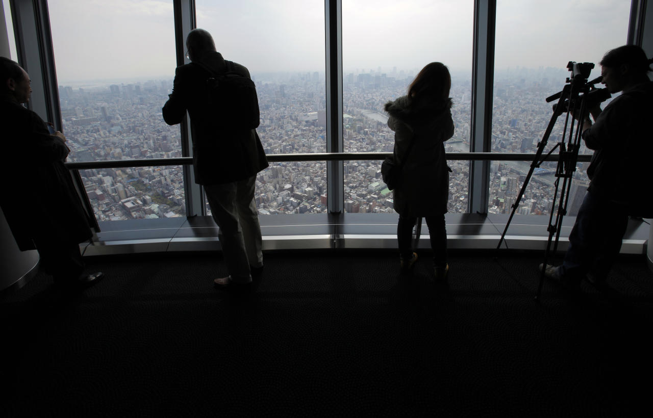 Journalists look at the view from the 450-meter (1,476 feet)-high observation deck of the Tokyo Sky Tree during a press preview in Tokyo Tuesday, April 17, 2012. The world's tallest freestanding broadcast structure that stands 634-meter (2,080 feet) will open to the public in May. (AP Photo/Itsuo Inouye)