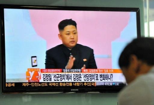 "A South Korean man watches a TV newscast reporting about the ""marshal"" title of North Korea's leader Kim Jong-Un"