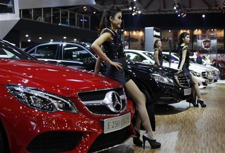 Models stand beside the Mercedes E250 Coupe during the 21st Indonesia International Motor Show in Jakarta