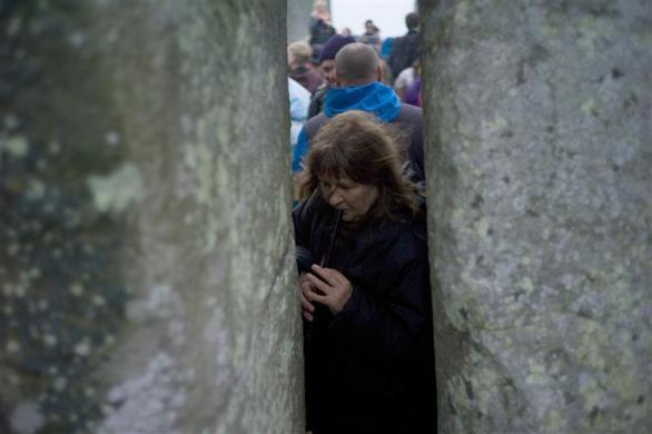 A reveler plays a flute between stones during the summer solstice at the ancient Stonehenge monument on Salisbury plain in southern England June 21, 2012.
