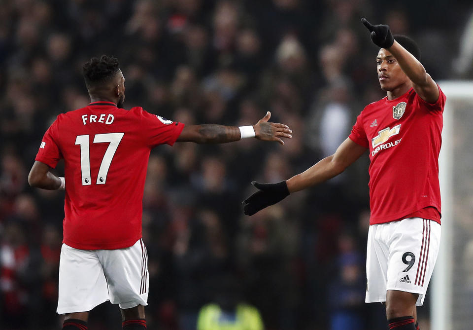 Manchester United's Anthony Martial, right, celebrates scoring his side's first goal of the game with teammate Fred during their English Premier League soccer match against Newcastle United at Old Trafford, Manchester, England, Thursday, Dec. 26, 2019. (Martin Rickett/PA via AP)