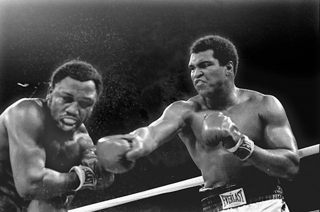 Sweat flies from the head of Joe Frazier as heavyweight champion Muhammad Ali connects with a right in the ninth round of their title fight in Manila, Philippines, in this Oct. 1, 1975 file photo. (AP Photo/Mitsunori Chigita)
