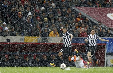 Arturo Vidal of Juventus (L) runs for the ball past Selcuk Inan of Galatasaray (bottom) during their Champions League soccer match in Istanbul December 10, 2013. REUTERS/Murad Sezer