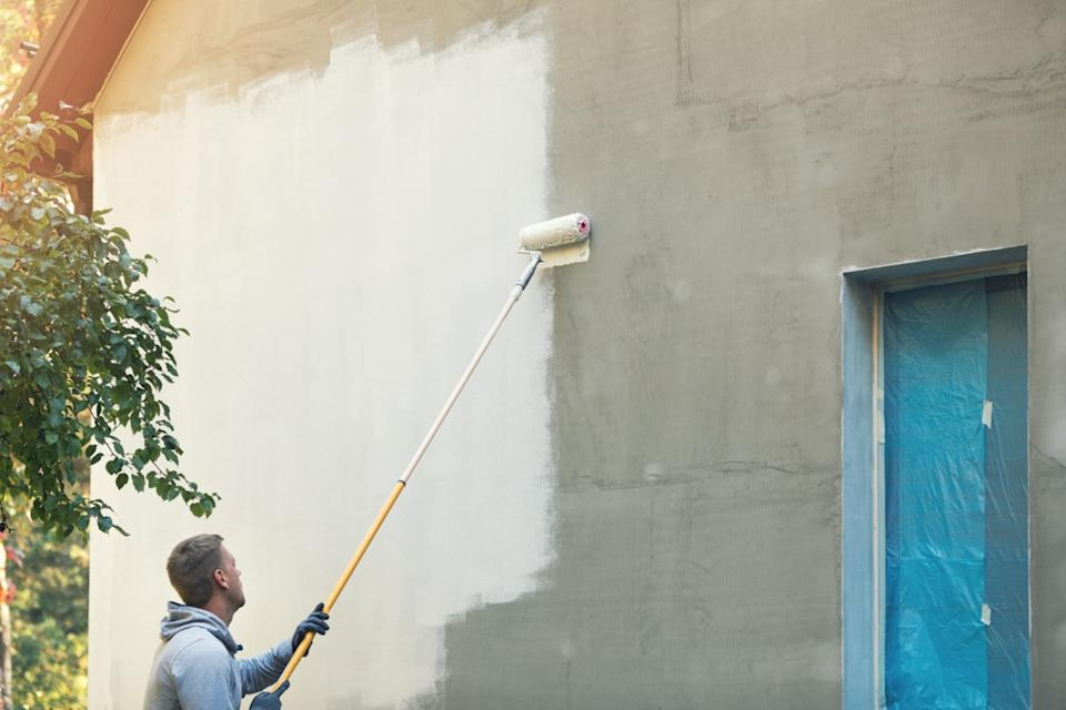 man painting home exterior white