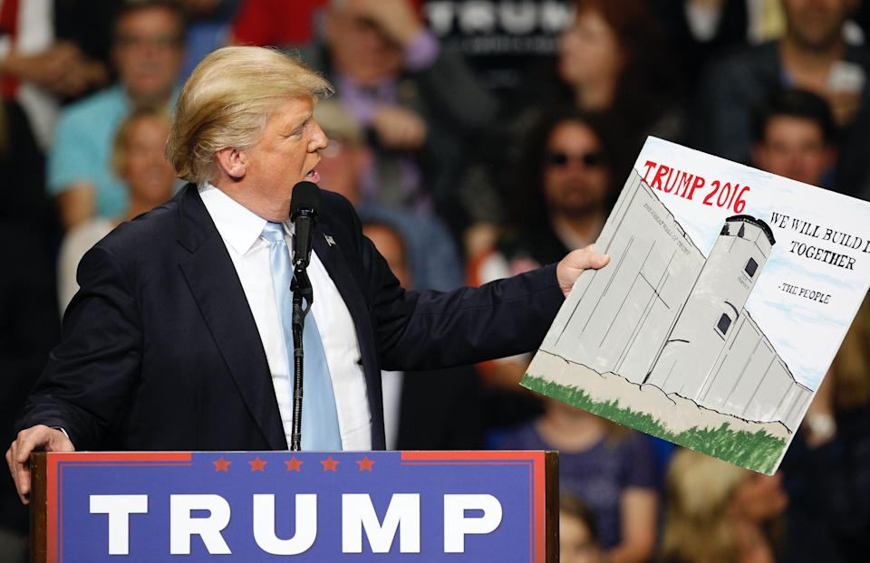Then-presidential candidate Donald Trump holds a sign supporting his plan to build a wall between the United States and Mexico in Fayetteville, North Carolina March 9, 2016. (Photo: REUTERS/Jonathan Drake)