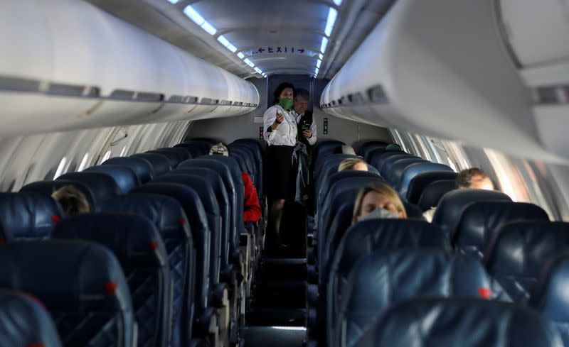 Flight attendants talk in a nearly empty cabin on a Delta Airlines flight operated by SkyWest Airlines
