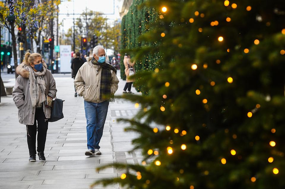 People wearing face masks pass Christmas lights outside shops on Oxford Street, London, as England continues a four week national lockdown to curb the spread of coronavirus.