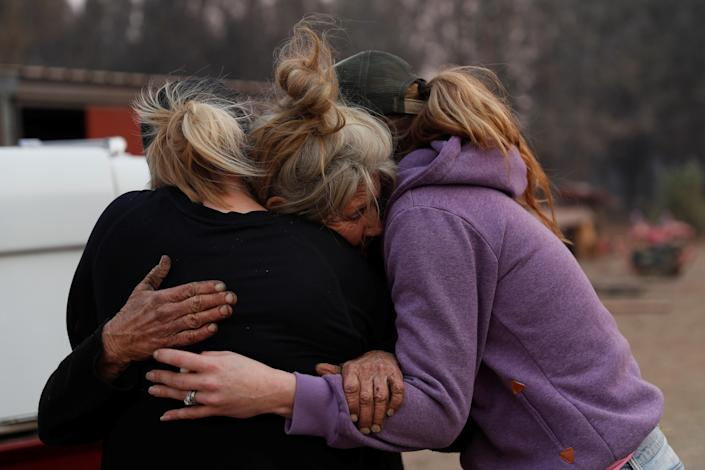 <p>Cathy Fallon, center, who stayed behind to tend to her horses during the Camp Fire, embraces Shawna De Long, left, and April Smith who brought supplies for the horses in Paradise, Calif., Nov. 11, 2018. (Photo: Stephen Lam/Reuters) </p>