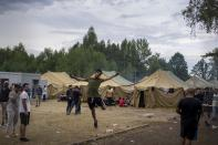 A migrant jumps as other walk inside the newly built refugee camp in the Rudninkai military training ground, some 38km (23,6 miles) south from Vilnius, Lithuania, Wednesday, Aug. 4, 2021. The Red Cross warned Wednesday that Lithuania's decision to turn away immigrants attempting to cross in from neighboring Belarus does not comply with international law. Lithuania, a member of the European Union, has faced a surge of mostly Iraqi migrants in the past few months. Some 4,090 migrants, most of them from Iraq, have crossed this year from Belarus into Lithuania. (AP Photo/Mindaugas Kulbis)