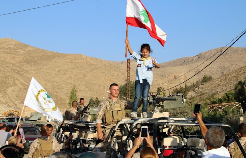 A girl scout waves a Lebanese flag next to a Lebanese army soldier during a celebration after troops returned from battling jihadists on the country's eastern border with Syria on August 30, 2017 (AFP Photo/STRINGER)