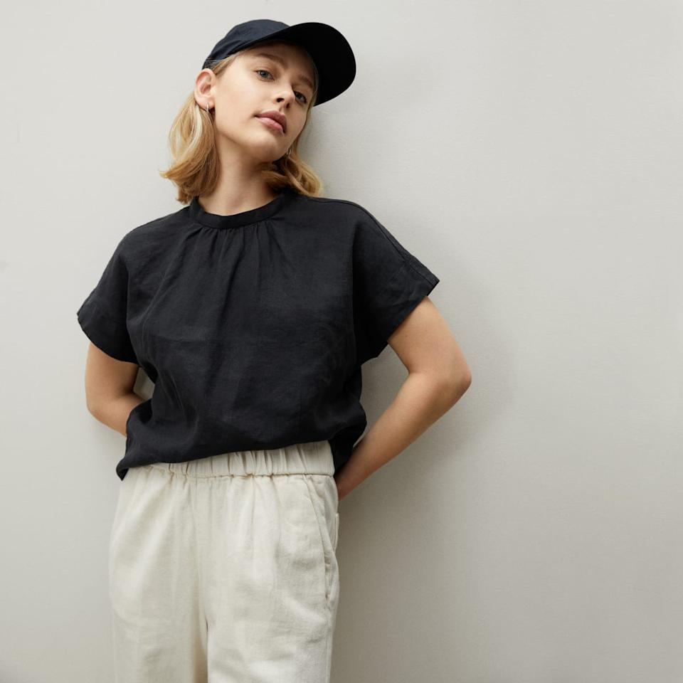 Model wears The Linen Drape Top in black with white pants and a black baseball cap. Image via Everlane.