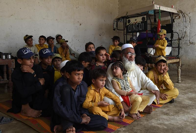 Pakistani father Gulzar Khan, 57, who has 36 children from his three wives, sits with his children