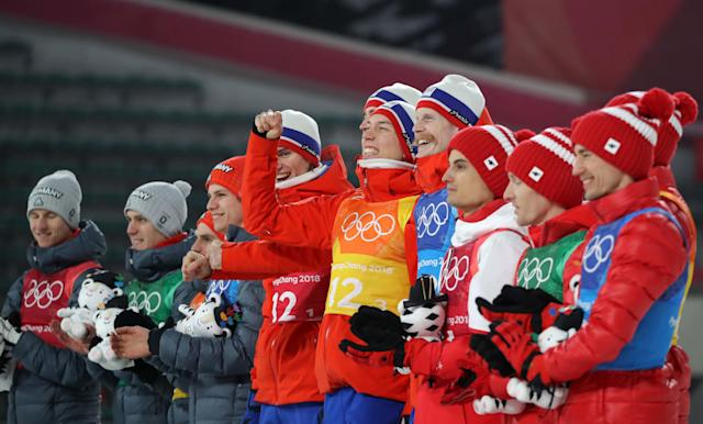Ski Jumping - Pyeongchang 2018 Winter Olympics - Men's Team Final - Alpensia Ski Jumping Centre - Pyeongchang, South Korea - February 19, 2018 - Gold medalists Daniel Andre Tande, Andreas Stjernen, Johann Andre Forfang and Robert Johansson of Norway, are flanked by Silver medalists Karl Geiger, Stephan Leyhe, Richard Freitag and Andreas Wellinger of Germany and Bronze medalists Maciej Kot, Stefan Hula, Dawid Kubacki and Kamil Stoch of Poland, as they celebrate during flower ceremony. REUTERS/Carlos Barria