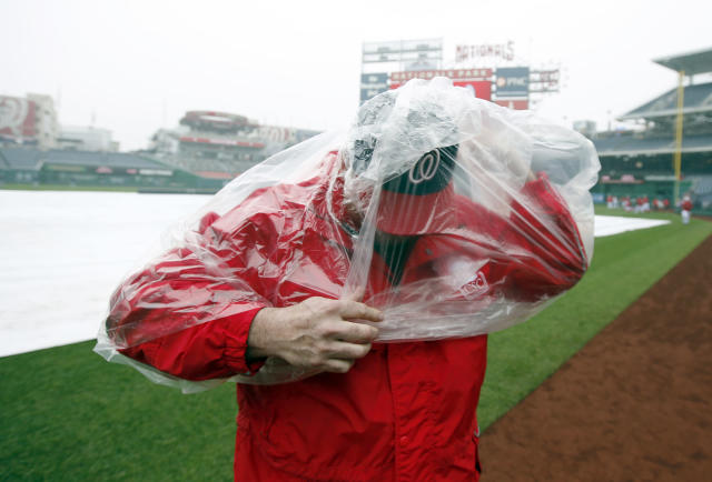 Bob Coleman, with field security, puts on his rain poncho before an exhibition baseball game between the Washington Nationals and the Detroit Tigers at Nationals Park Saturday, March 29, 2014, in Washington. The game was canceled due to weather. (AP Photo/Alex Brandon)