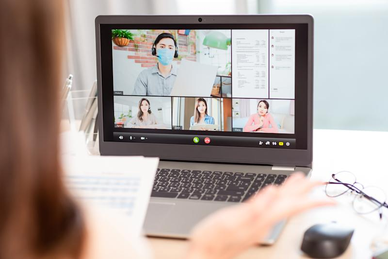 telework concept - Back view of asian woman use laptop to join a video meeting and her team member is self quarantine at home because coronavirustelework concept - Back view of asian woman use laptop to join a video meeting at home