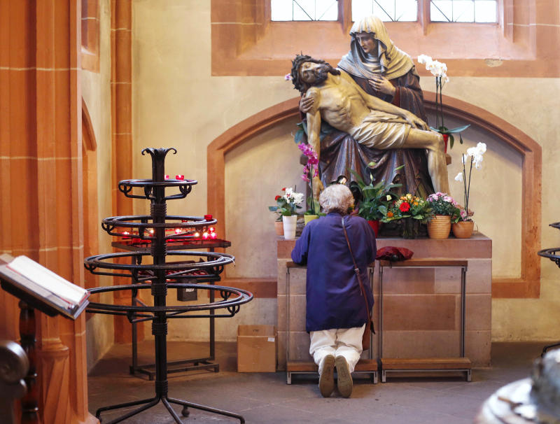 In this photo taken on Thursday, Sept. 27, 2012, a woman prays under a statue depicting Jesus and Mary, in the cathedral of Frankfurt, Germany.  The road to heaven is paved with more than good intentions for Germany's 24 million Catholics. If they don't pay their religious taxes, they will be denied sacraments, including weddings, baptisms and funerals.  A decree issued last week by the country's bishops cast a spotlight on the longstanding practice in Germany and a handful of other European countries in which governments tax registered believers and then hand over the money to the religious institutions.  (AP Photo/Michael Probst)