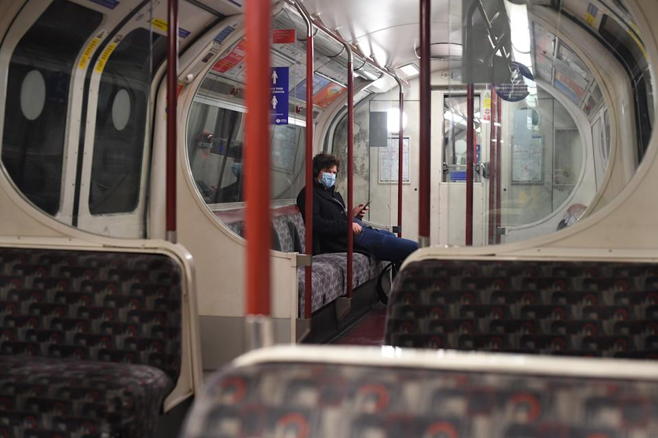 A man sits alone on a Bakerloo Line underground train in central London. Prime Minister Boris Johnson cancelled Christmas for almost 18 million people across London and eastern and south-east England following warnings from scientists of the rapid spread of the new variant coronavirus.