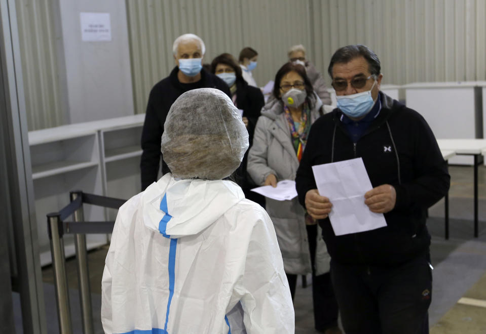 People wait in line to receive a dose of Chinese Sinopharm COVID-19 vaccine during the vaccination at Belgrade Fair makeshift vaccination center in Belgrade, Serbia, Wednesday, Feb. 17, 2021. Serbian health expert Chief epidemiologist Predrag Kon on Tuesday March 2, 2021, called for the government to introduce a state of emergency and a strict lockdown to halt a surge in coronavirus infections in the Balkan country. (AP Photo/Darko Vojinovic)