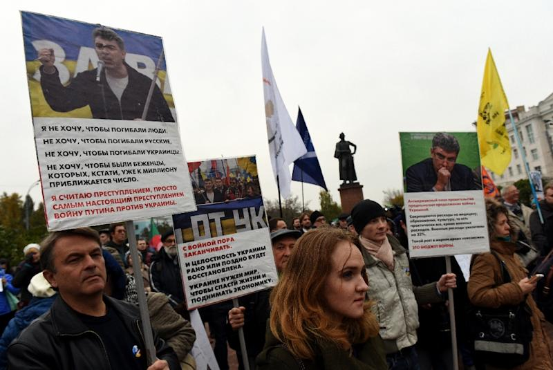 Demonstrators hold banners bearing portraits of assassinated Russian opposition leader Boris Nemtsov, during an antiwar rally in central Moscow