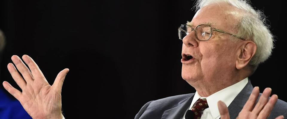 Warren Buffett speaks with hands up