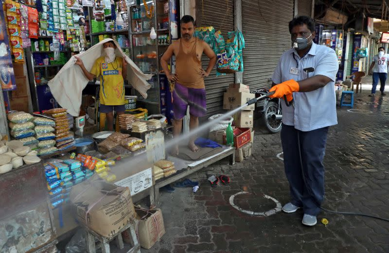 A municipal worker disinfects a pavement in a market area during a 21-day nationwide lockdown to limit the spreading of the coronavirus disease (COVID-19), in Kolkata