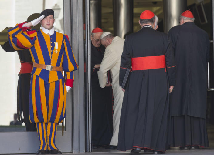 """A Vatican Swiss Guard salutes as Pope Francis is welkomed by cardinal Agostino Vallini as he arrives to open the morning session of an extraordinary consistory in the Synod hall at the Vatican City, Friday, Feb. 21, 2014. Pope Francis is leading a two-day meeting urging his cardinals to find """"intelligent, courageous"""" ways to help families under threat today without delving into case-by-case options to get around Catholic doctrine. He said the church must find ways to help families with pastoral care that is """"full of love.""""(AP Photo/Alessandra Tarantino)"""