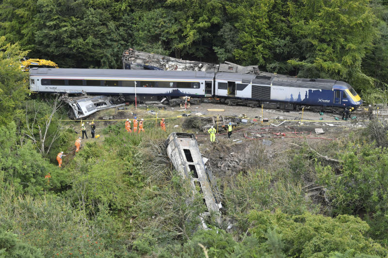 Emergency services inspect the scene following a train derailment near Stonehaven, Scotland, Thursday, Aug. 13, 2020. British Transport Police say three people died and six were taken to the hospital with injuries after a passenger train derailed in northeast Scotland after heavy rain and flooding. The train driver and conductor are believed to be among the dead, but formal identification is pending. (Ben Birchall/PA via AP)