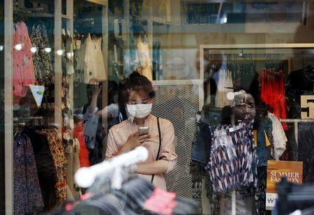 A woman wearing masks to prevent contracting Middle East Respiratory Syndrome (MERS) uses her mobile phone inside a clothing shop in central Seoul, South Korea, June 16, 2015. REUTERS/Kim Hong-Ji