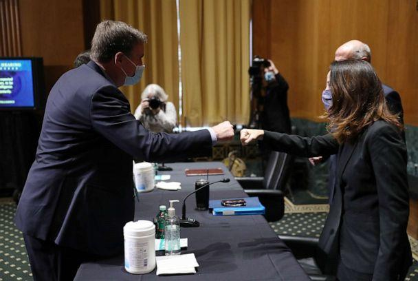 PHOTO: Avril Haines, right, bumps fists with Sen. Mark Warner before the start of the Senate Intelligence Committee confirmation hearing to be President-elect Joe Biden's pick for national intelligence director on Jan. 19, 2021, in Washington. (Joe Raedle/Getty Images)
