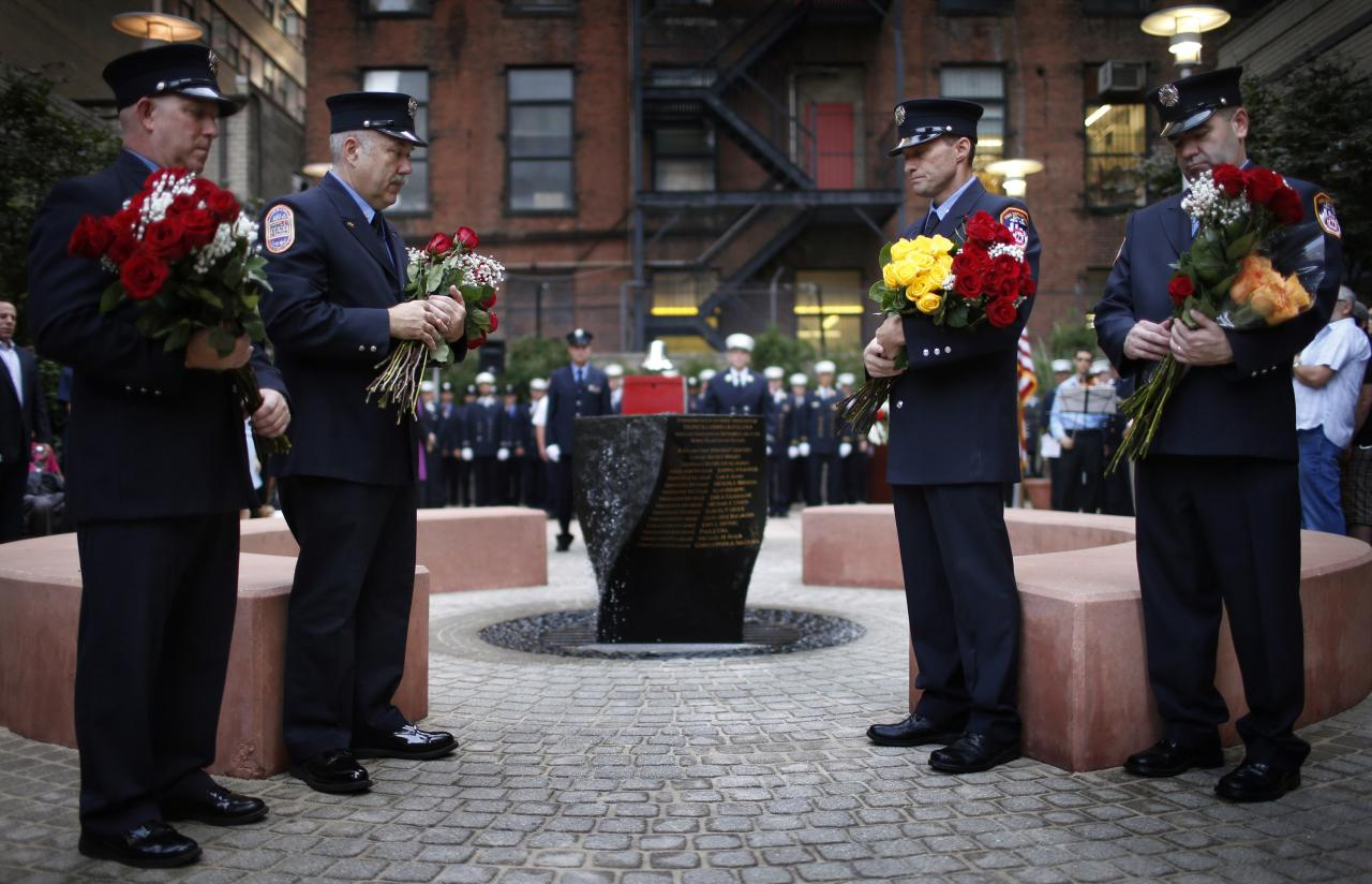 New York City firefighters from Engine 54, Ladder 4, Battalion 9, hold flowers during a ceremony at a park dedicated to honoring members of the firehouse on West 48th Street who lost their lives in the September 11, 2001 attacks on the World Trade Center on the 12th anniversary of the attacks in New York, September 11, 2013. 15 fire fighters from Engine 54, Ladder 4, Battalion 9 died in the 9/11 attacks, the most of any fire company in New York. REUTERS/Mike Segar (UNITED STATES - Tags: DISASTER ANNIVERSARY)