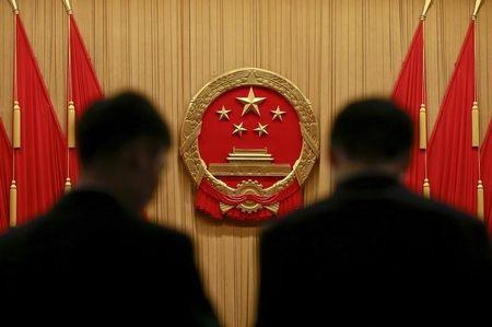 Security officers stand near the Chinese national emblem as they carry out a check after delegates left at the end of the opening session of the National People's Congress (NPC) at the Great Hall of the People in Beijing, China, March 5, 2016. REUTERS/Kim Kyung-hoon