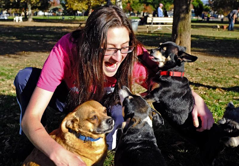 In this Saturday Nov. 30, 2013 photo, Cambria Hankin talks to her three dogs, from left to right, Buddy, Riah and Stitch, at the Sepulveda Basin Dog Park in the Encino section of Los Angeles. Dr. Gary Weitzman, president of the San Diego Humane Society, has worked with tens of thousands of stray dogs over the last quarter century and says there is no question that pets and people communicate. Wags and barks speak volumes when it comes to understanding what a dog is saying, but there are also clues in a dog's eyes, ears, nose or the tilt of its head. (AP Photo/Richard Vogel)