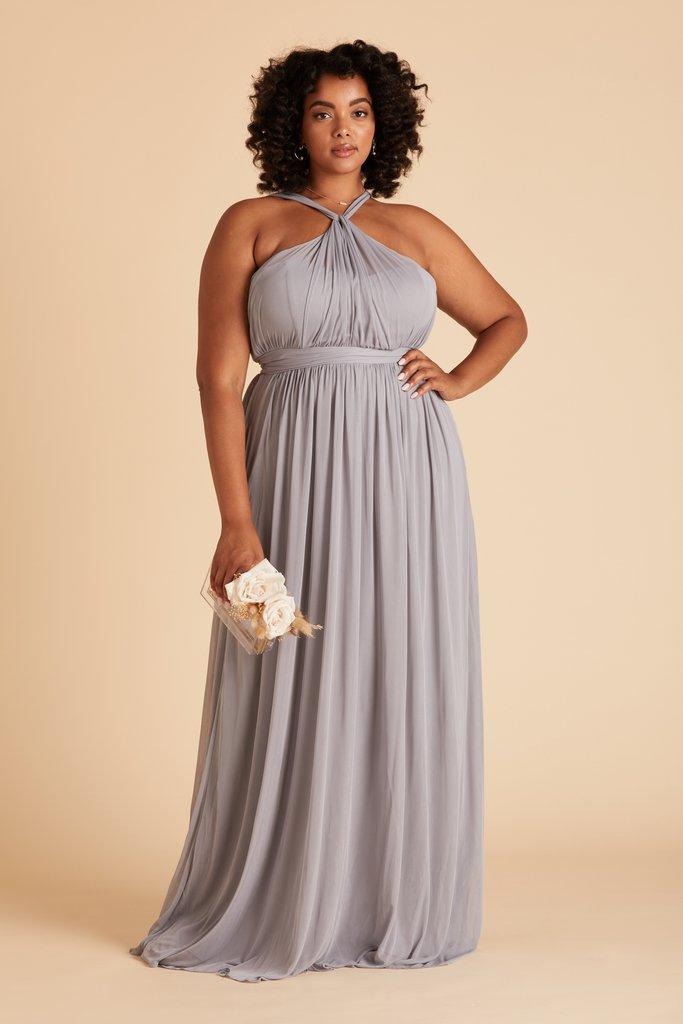 black plus size model with curly hair posing in light purple/grey bridesmaids dress