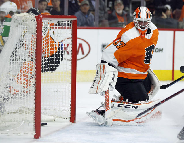 Philadelphia Flyers goalie Brian Elliott looks back towards the puck after Pittsburgh Penguins' Phil Kessel scored during the first period in Game 4 of an NHL first-round hockey playoff series Wednesday, April 18, 2018, in Philadelphia. (AP Photo/Tom Mihalek)