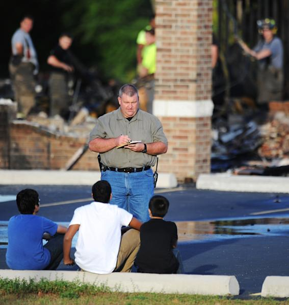 An investigator asks questions of witnesses as firefighters work in the background after a fire at the Islamic Society of Joplin mosque, Monday, Aug. 6, 2012, in Joplin, Mo. The fire was the second fire to hit the Islamic center in little more than a month. The boys, pictured from left, are: Haaris Rehman, 12; Omar Ahmed, 15; and Humza Rehman, 10. (AP Photo/The Joplin Globe, T. Rob Brown) MANDATORY CREDIT