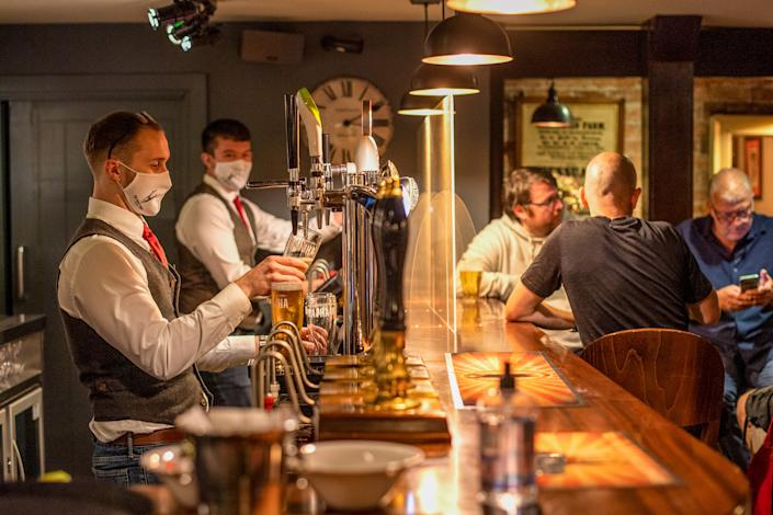 Bartenders at the White Heart Pub and Restaurant in Lydgate, Oldham, in July 2020. (Anthony Devlin/Bloomberg via Getty Images)